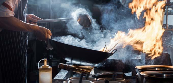Kock som lagar mat med stekpanna